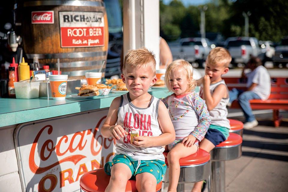 Kids sitting on stools at Eddie's Grill stools